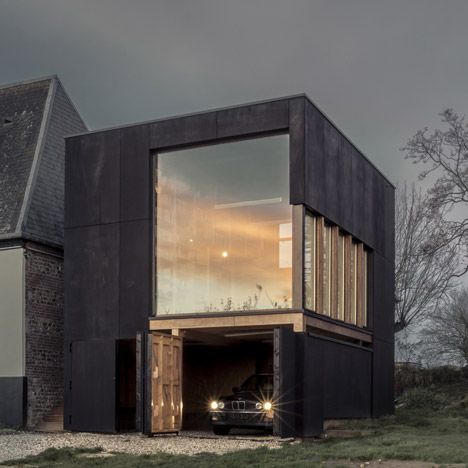 A blackened plywood box connected to one end of a rural home on France's northern coast provides a private library and garage for its inhabitants.