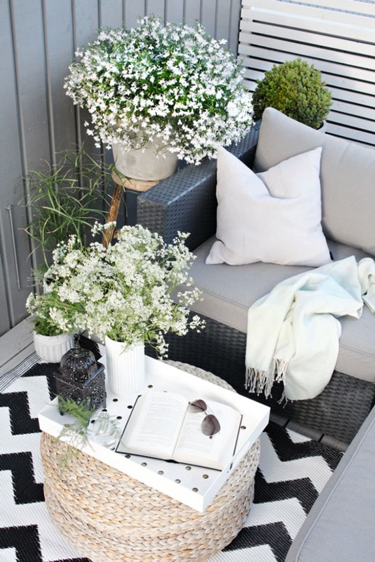 Scandinavian outdoor balcony with serving tray, cushions, blanket, and flowers