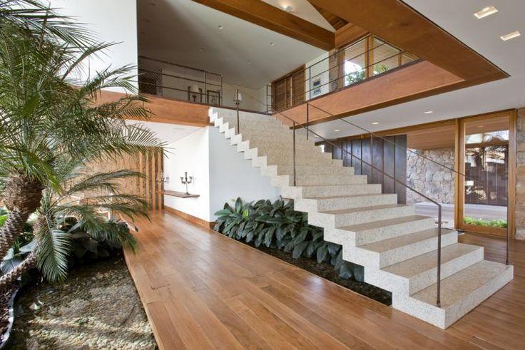 Casa de Pedra, projeto de Erick Figueira em Bragança Paulista, São Paulo, Brasil. Hall central e escadaria. Fotografia: Divulgação / Casa e Decoração / UOL Mulher. Mais