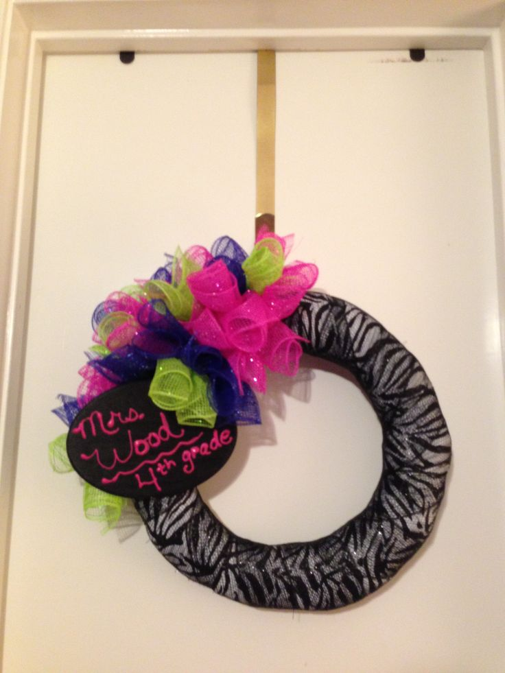 """My new wreath for my classroom. I used a zebra patterned sheet for fabric, cut it in strips, and covered a straw wreath. Then I covered the fabric with black deco mesh. The """"bow"""" is pink, lime green and blue deco which I cut into little strips and rolled. I made a hook out of the sheet and glued it on the back to hang it. I bought an oval wooden plaque, painted it with chalkboard paint and then used fabric paint to write my name on it. Total cost about $10.00. A Pinterest inspired project."""