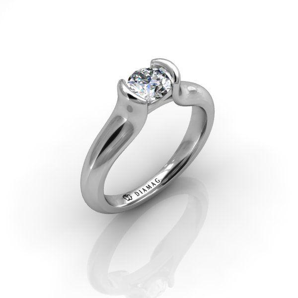 Acest inel simplu și elegant din aur alb pune în valoare diamantul central, datorită monturii semi-bezel, care nu împiedică lumina să ajungă la piatră. Este perfect pentru cei care nu-și doresc un inel cu diamantul montat pe gheruțe, dar vor un inel care să iasă în evidență. Poate fi comandat cu diamant rotund de orice dimensiune.