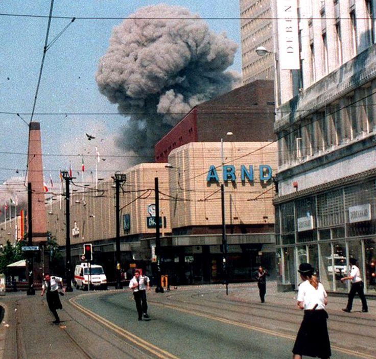 Greater Manchester police officers react in the immediate aftermath of the 15 June IRA terrorist bombing outside the Arndale Centre, the enormous mushroom cloud caused by the terror attack rising only a block away, Manchester, England, United Kingdom, 1996, photographer unknown.