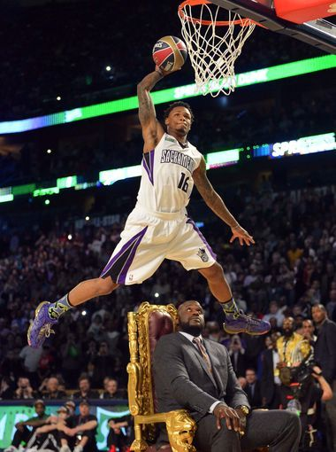 Kings guard Ben McLemore jumps over NBA legend Shaquille O'Neal for a slam during the dunk contest.