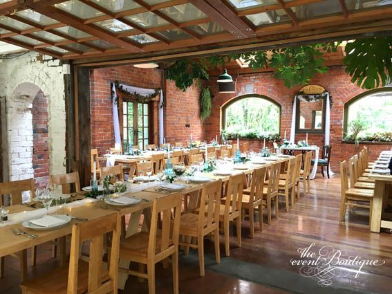 Reception tables styled at Trents Vineyard with soft unstructured muslin falling from the tables, clustered groups of candles and flowers with the sweetheart table framed by the voile.