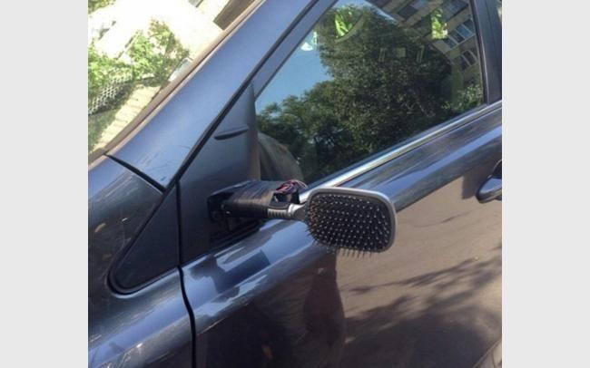 una spazzola per capelli in sostituzione dello specchietto dell'automobile rotto