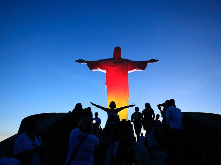 Pose with the massive statue of Christ the Redeemer on Corcovado Mountain in Rio de Janeiro, Brazil.