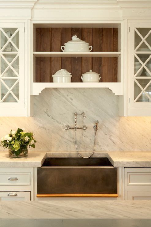 Elegant traditional kitchen features x mullion cabinets over inset cabinets and drawers paired with white carrera marble countertops and a white carrera marble slab backsplash flanking a metal apron sink paired with a wall-mounted bridge faucet under open shelves lined with a stained beadboard backsplash.