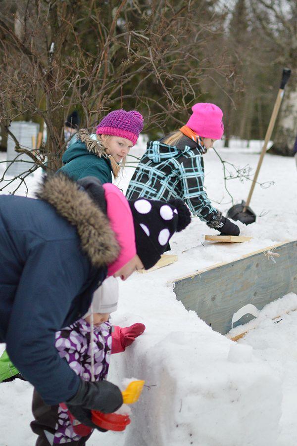 Muurin rakentavat isot ja pienet kädet yhtä ketterästi. Rakennustyön jälkeen maistuu kuuma kaakao. Oulu (Finland)