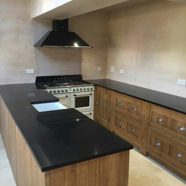 This traditional U shape kitchen is made up of the Nero De Lusso and brown wood cabinetry. The black quartz is the perfect colour to add an instant glamour appeal to this traditional style kitchen.
