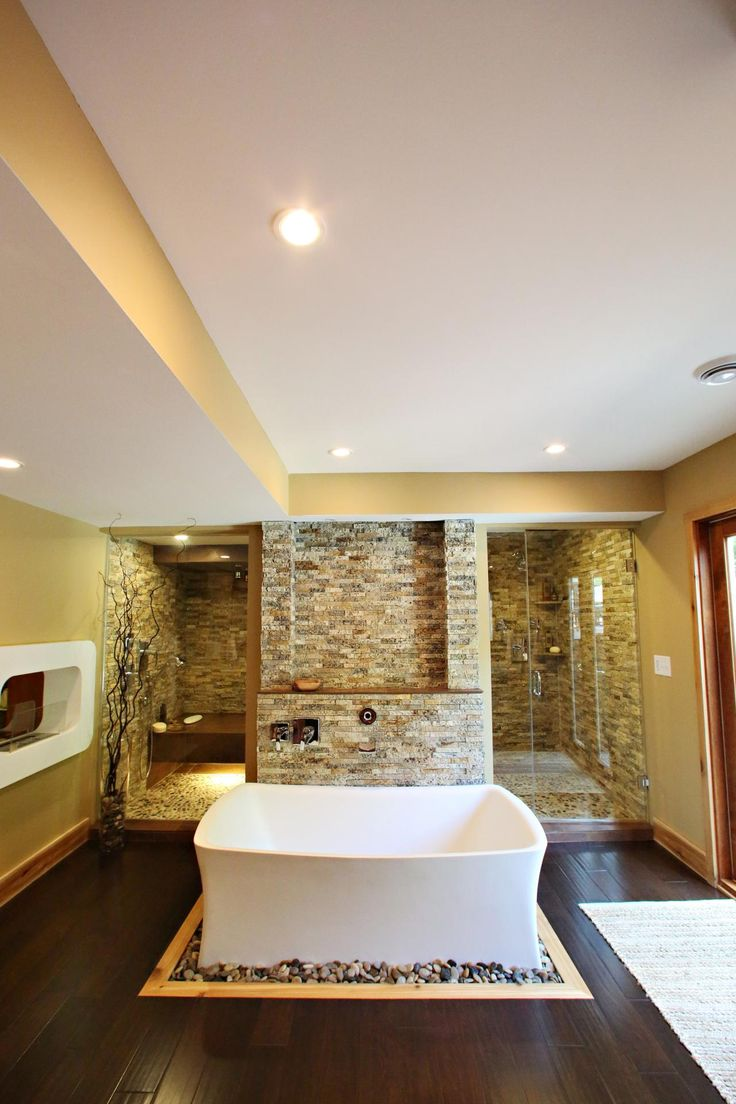 As seen on HGTV's Bath Crashers, a contemporary spa bathroom features a stone accent wall, walk-in sauna and shower as well as luxurious soaking tub.