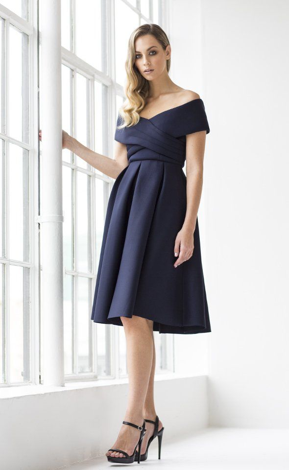Make a fashionable entrance at your next event in this statement bardot dress. Fabricated from a thick scuba this style features a crossover bodice detail and fit and flare silhouette. This piece is party perfect for your next special event.