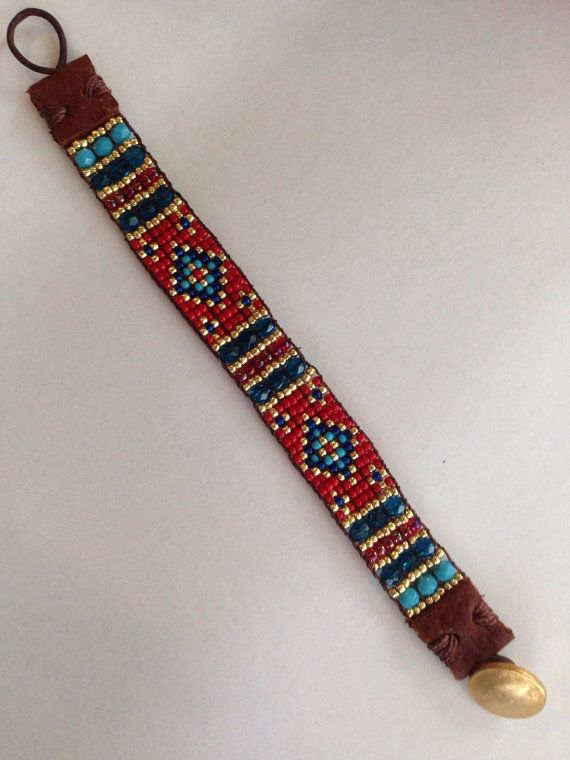 Very Eye Catching Red Stunner Hand Loomed Sundance Style Bracelet. Use Zoom Under Photos to See Detail. Red, Turquoise, Blue Teal, Royal Blue, and Gold. Faceted Glass Czech Beads, Seed Beads With Leather End Tabs And Gold Button Closure.  Quality Made. Very Durable.  Measures 7 1/4 Inch In Total Length Width-5/8 Inch Will Fit Wrist Size Up To 6 1/2 Inches This Is Not Adjustable. Ready For Gift Giving Ships In A Very Cute Bracelet Gift Box. Ships Priority One Mail. Listing Green D-1.