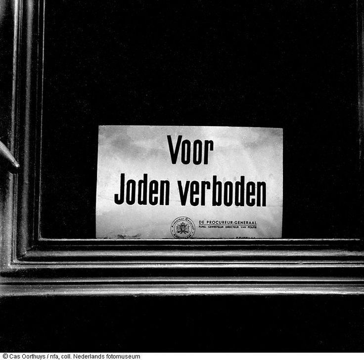 Achter een venster is in de hongerwinter een pamflet met de tekst 'Voor Joden verboden' aangebracht, Amsterdam, (1944-1945)