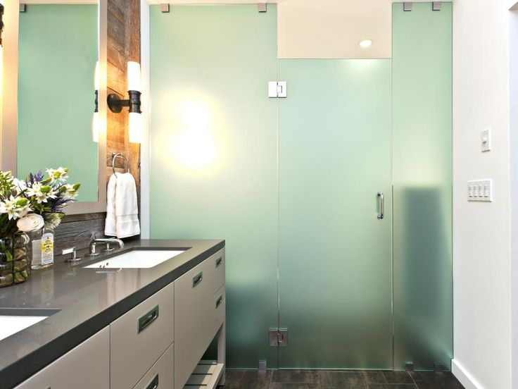 An opaque glass-enclosed shower is adjacent to a long taupe vanity that has two built-in sinks and large mirror. Soft lighting in the room is provided by a sconces near the vanity and recessed lighting in the shower to create a tranquil, relaxing space.