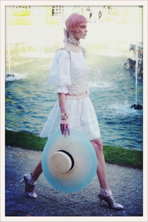 Robe de bal immaculée, capeline en paille et catogan fluo, au défilé Chanel croisière 2013 qui avait lieu dans les jardins du château de Versailles. Une collection inspirée du style Marie-Antoinette version techno.