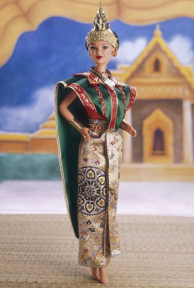 As beautiful and exotic as the land she represents, Thai Barbie doll is ready to perform a traditional dance, called the Lacon, in her ceremonial costume. Her headdress resembles a golden Wat (temple). Her shiny green cape has golden and red highlights and her multicolored skirt has a golden belt and sash. She has golden bracelets on each arm and her feet are bare, just like a Thai dancer!