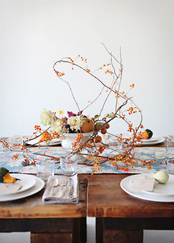 Free form whimsical autumn arrangement with bittersweet branches