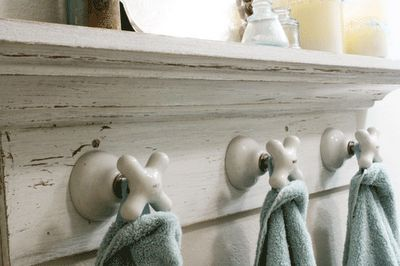 Old porcelain faucets repurposed as towel hooks. @Marilyn Shipps we have that huh!