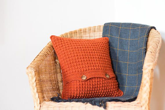 Created using a textured crochet stitch, this burnt orange cushion cover works well alongside other boho cushions. It makes a lovely throw pillow on a sofa and adds a bright accent of colour to a room.  DETAILS AND FEATURES  - Created using a textured crochet stitch. - Features an envelope opening fastened with two coconut shell buttons. - Made from 100% acrylic yarn. - Designed to tightly fit a 40x40cm (16 inch) cushion to keep your cushion nice and plump. This is not included but is a…