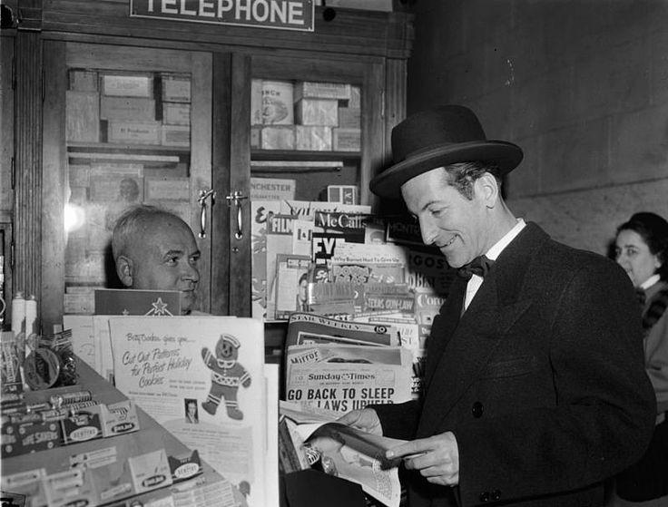 Le comédien Jean-Pierre Masson feuilletant une revue devant un kiosque à journaux à Montréal. 1949. BAnQ, P48,S1,P23512