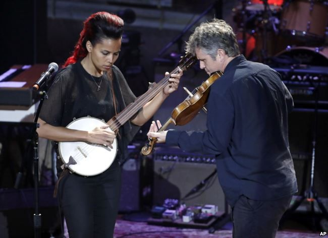Rhiannon Giddens, left, performs with Dirk Powell during the Americana Honors and Awards awards show, Sept. 13, 2017, in Nashville, Tennessee.
