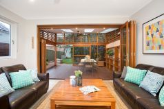 Family living area, covered outdoor entertaining area, lounge, wall art, coffee table, bi fold doors