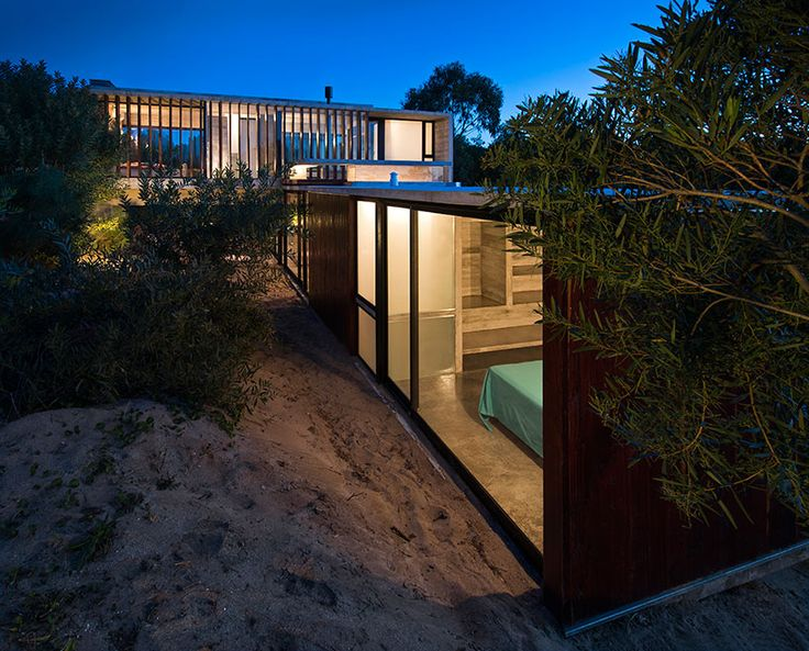 two overlapping concrete volumes project a functional home suited for its unique dune environment, enjoying the landscape throughout the interior.
