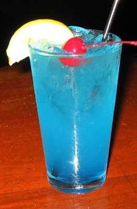 """""""Blue Long Island Iced Tea""""  First thing is find a Hurricane glass and fill it with ice. After that add what I like to call the """"Fantastic Four"""" which consists of 1/2 oz each of Vodka, Gin, Rum & Tequila. Add 1/2 oz of Blue Curacao and almost fill with sweet & sour mix. Make sure to add a splash of 7up and a garnish which should be a lemon wedge and Enjoy."""