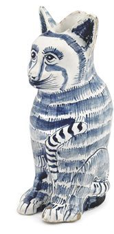 A LONDON DELFT BLUE AND WHITE CAT-JUG CIRCA 1660, TRACES OF BLUE MARK TO BASE Modelled as a tabby cat seated on his haunches, his striped tail curved beneath his legs and moulded up his chest, with striped fur, whiskers and face markings, the lip to the jug behind the cat's ears