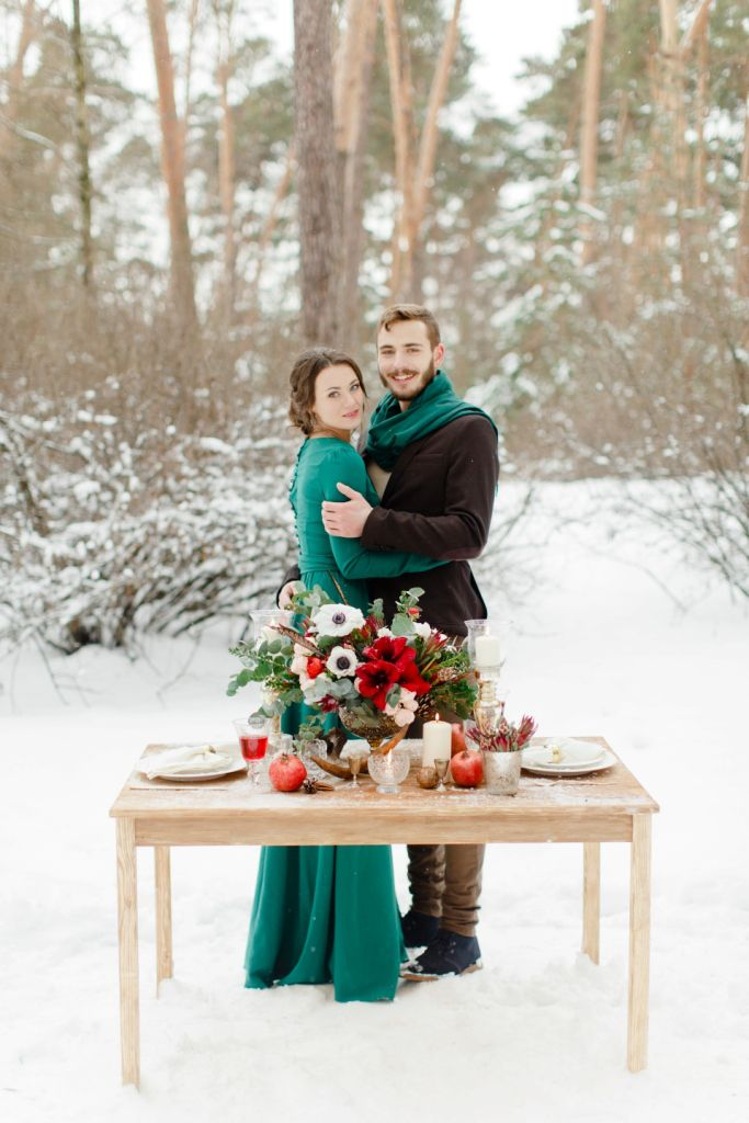 beautiful couple on the background of the decorated table, red emerald shooting