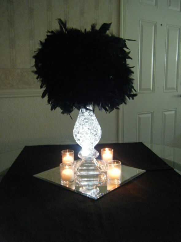 100 gram feather boa (Ebay) = $4.60  1 Vase = $15.00  5 inch styrofoam ball (Save-on-crafts) = $2.59  12 inch beveled mirror (Home depot) = $3.33  white LED floralyte = $2.00  water pearls  Votives  Total Cost = under $30.00 each