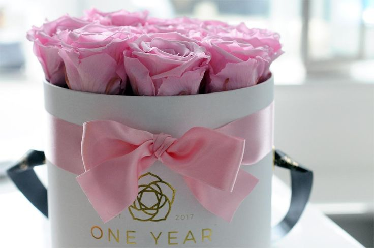 Pink roses that last for 1 year in a white hat box, with a pink satin ribbon tied in a bow.