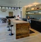 Zwarte keuken met een mooi steigerhouten kookeiland en leuke krukken.
