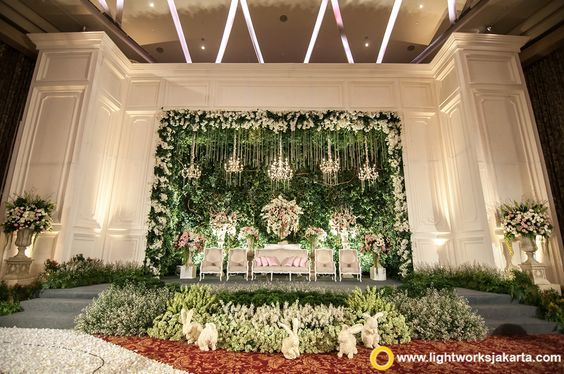 ♥ this pretty white and green stage concept with a vertical garden backdrop paired with lounge queen arm furniture complete with a mini garden with floral rabbits in front! So cute!| Curated by Witty Vows – Things No one tells brides |The ultimate guide for the Indian Bride to plan her dream Indian wedding. Real weddings, ideas, trends, recomendations and inspiration | ♥ ♥ ♥ | Photo - @lightworksjakarta | #reception #engagement #stage #backdrop #inspiration #IndianWedding | www.wittyvows.com