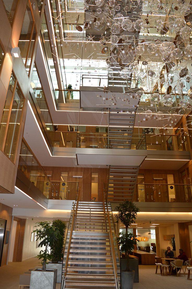 Le pareti e i pavimenti di legno contrastano in maniera affascinante con elementi come la copertura e la facciata in vetro nell'atrio. Nella scala principale che collega tutti i piani dell'edificio, le balaustre in vetro fanno da contrappunto alle scale in legno e ai corrimani in rovere.