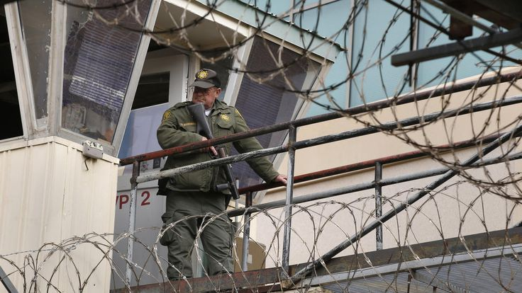 A guard watches the movement of the prisoners being escorted across the yard at San Quentin State Prison