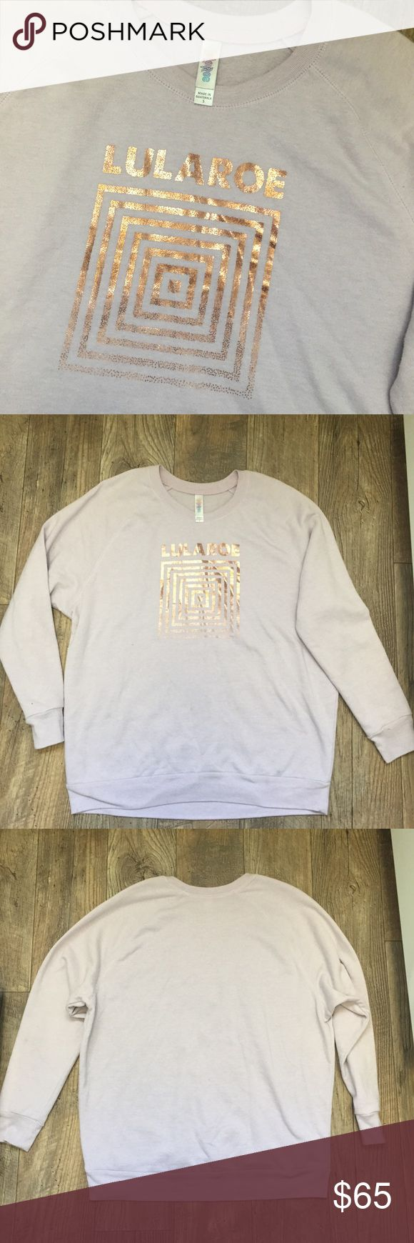 """Lularoe Lavender Gold Square Logo Sweatshirt Small Lularoe Women's Lavender Purple Metallic Rose Gold Square Logo Sweatshirt Small  Women's size S measures 46"""" bust, 40"""" waist, 27"""" length  Runs big, would fit a women's medium  50% Cotton 50% Polyester  Very gently worn- no rips holes or stains!  Awesome Rare item! Perfect to pair with your favorite leggings! LuLaRoe Tops Sweatshirts & Hoodies"""