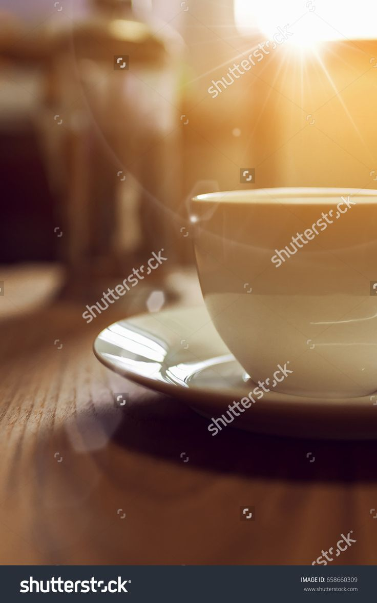 Abstract blur image background of a coffee in the morning with white cup on wooden board and sunlight from window in the bedroom (warm tone), Retro filtered