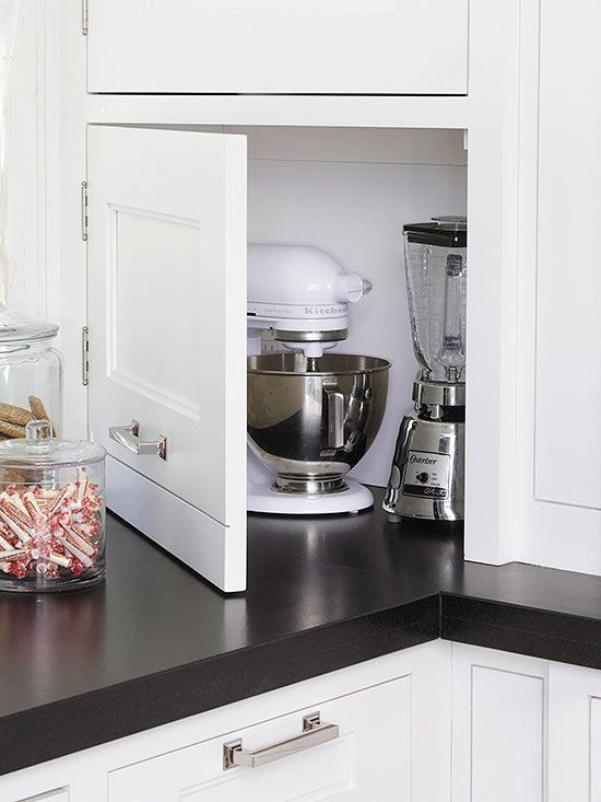 Avoid an overly industrial look in your kitchen by hiding the microwave oven, toaster, blender, and other tabletop appliances in an appliance garage with a door./