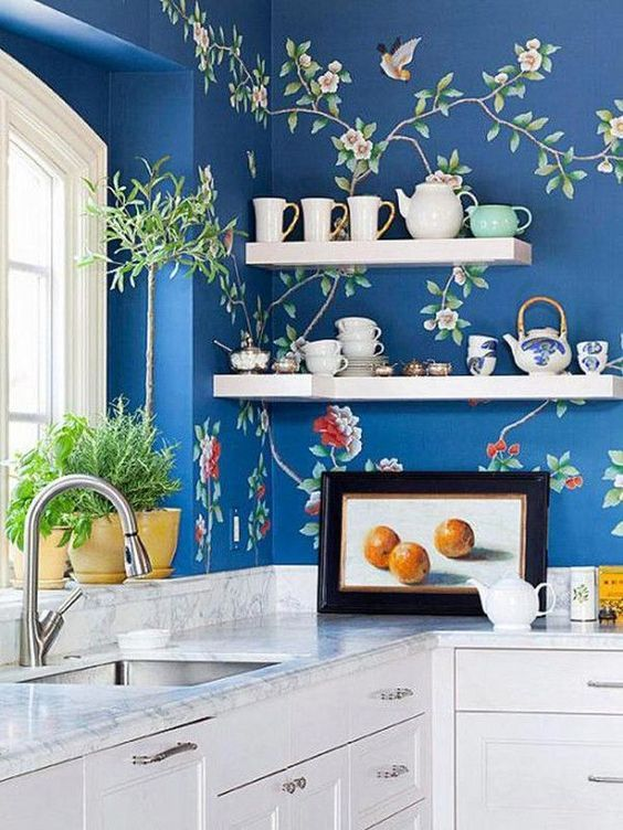 Domino A blue Chinoiserie wallpaper is a bold choice in this white kitchen.