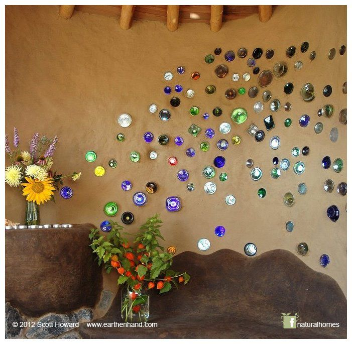 This is the beautiful work of Scott Howard [www.earthenhand.com]. It's in the little kindergarten cob play room at the New Day School [www.newdayschool.org] in Portland, OR, USA. Those bottles in the wall are just wonderful, like pollen blowing off the flowers in a strong breeze. Scott's workshops for this year are on his website here: www.earthenhand.com/workshops