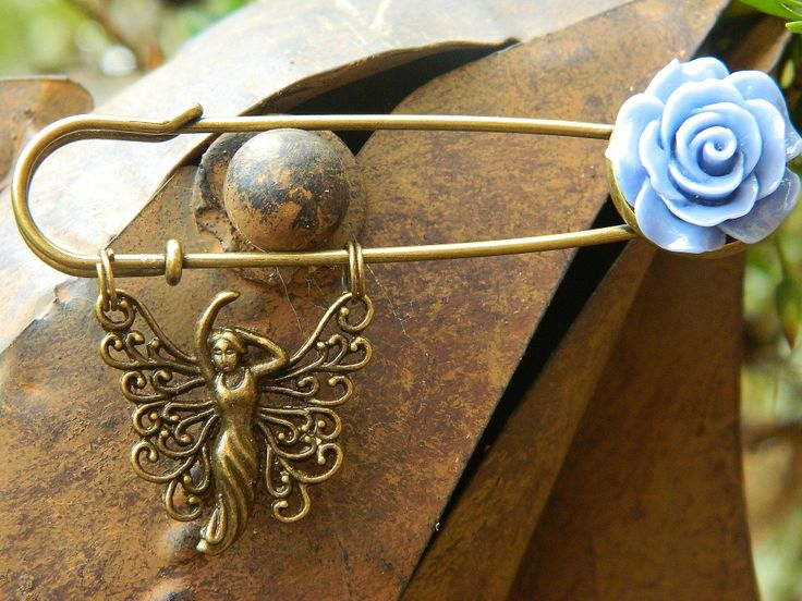 Goddess Kilt Pin. Metal alloy kilt pin and charm in antique bronze. Resin flower. Length 7.5 cm, width 4 cm (includes width of pin and charm), depth 1cm. I have used bronze tone metal alloy split rings to connect charm.  https://www.madeit.com.au/Main/Item?itemId=956793