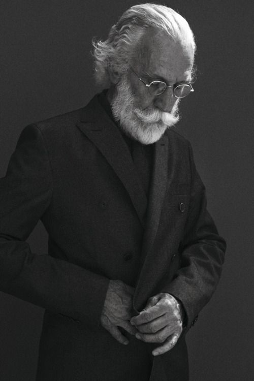 the hair, the beard+moustache, the glasses, the downcast eyes, the pose, the weathered hands, the charcoal on black, the light --- loving everything about this photo