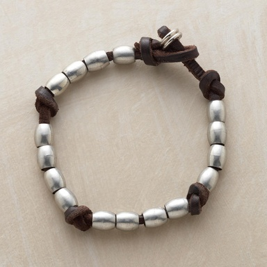 "KNOT AND BEAD BRACELET -- Beads and knots tame dark brown leather cords for the wearing. Threaded with pewter beads. Unmistakably Colonel Littleton, handmade in USA with loop and ring closures. Made in USA. Approx. 9""L."