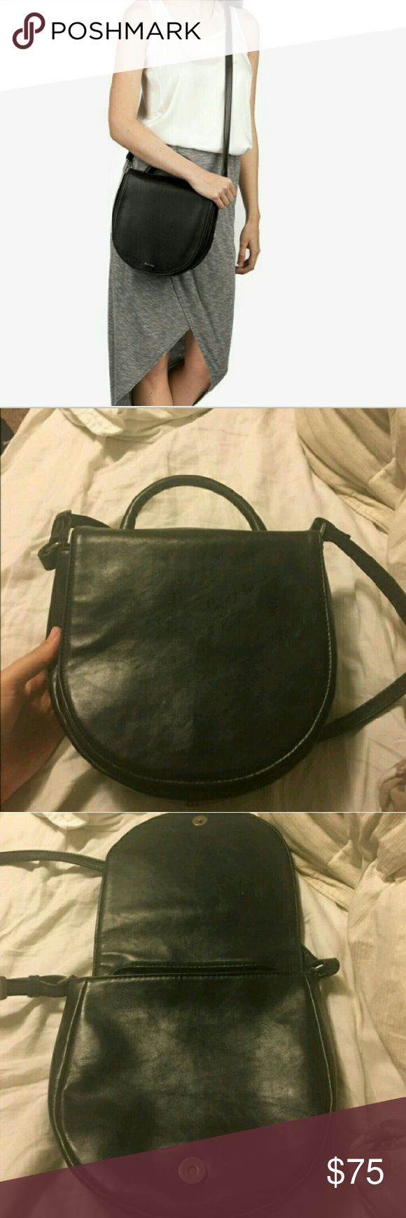"""Matt and Nat Vegan Leather Parabole Saddlebag Incredibly stylish and pretty utilitarian for its size. If you haven't tried it out, Matt and Nat is a great brand for those looking for high quality without the leather or the leather price tag! Sold at Urban Outfitters, Nordstrom, and other fine retailers. This bag has been loved, but aside from some wrinkling (pictured), it's like new!  9"""" x 8.5"""" x 3.25"""" with a 19-24"""" adjustable strap. Matt and Nat Bags Crossbody Bags"""