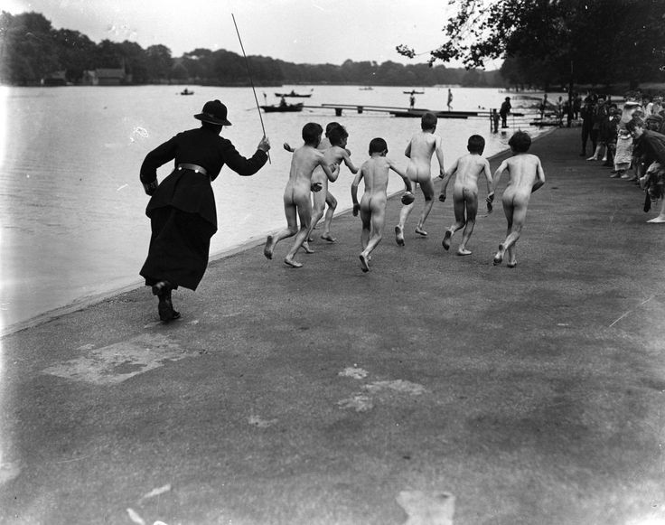 Police officer chases down a group of young skinny dippers in Hyde Park. 1926