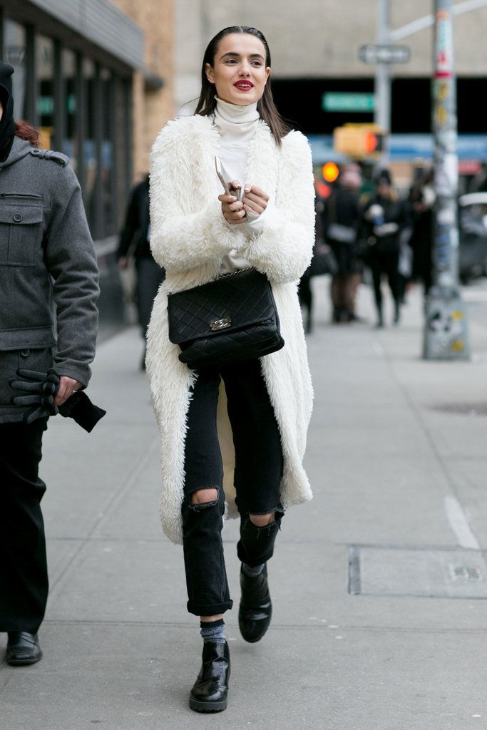 A fluffy coat paired with distressed jeans and a Chanel purse.