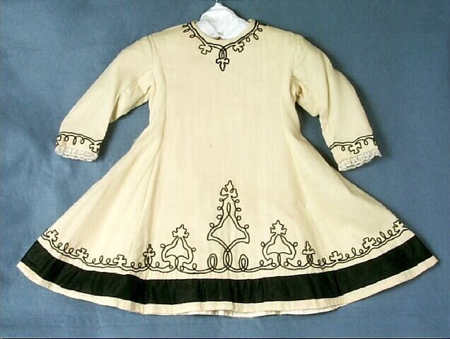 Dress, girl's, pale yellow wool, black soutache trim, c. 1873