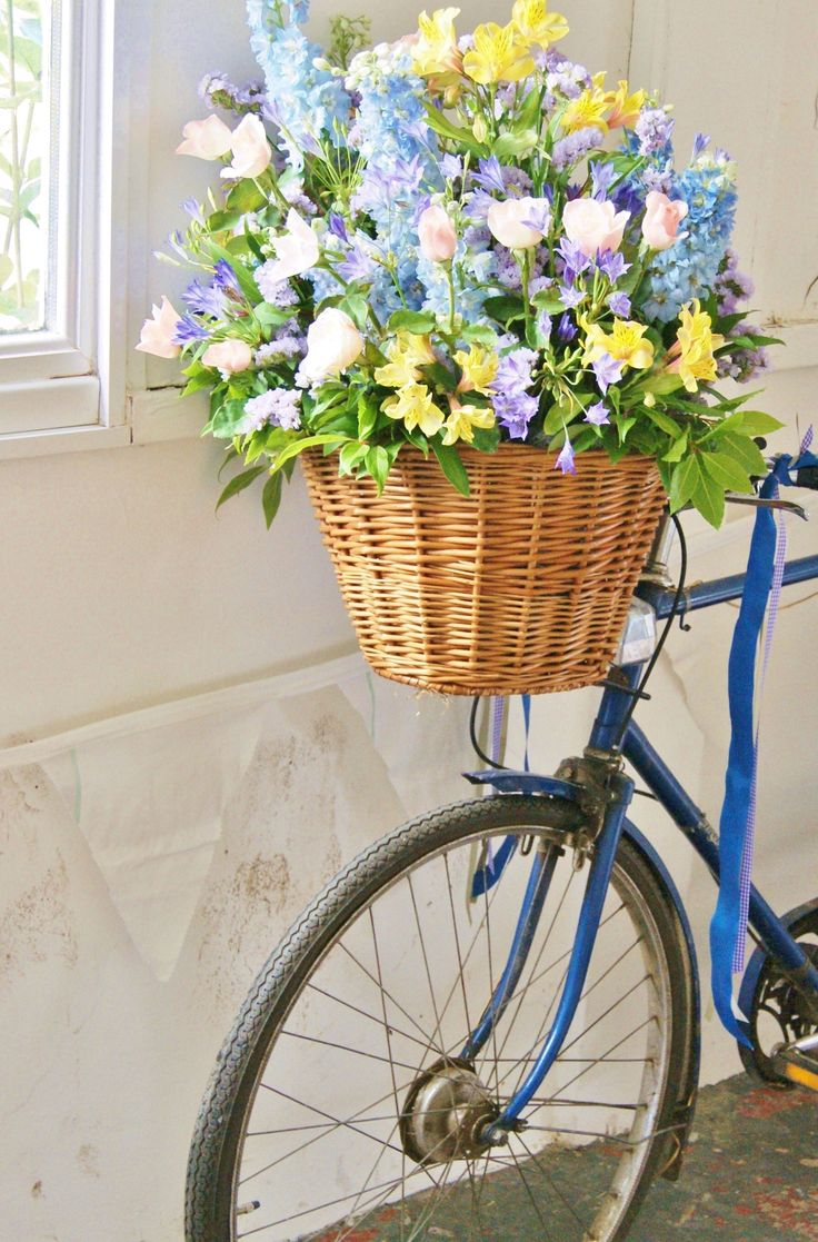 Bike with rustic British-grown flowers - peach roses, blue delphinium, yellow alstroemeria, blue brodiaea, pale purple statice and colourful ribbons - fantastic for a Bohemian, festival-themed wedding. Florissimo, Shropshire