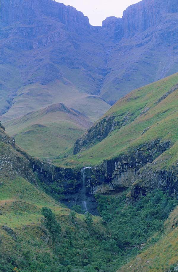 Waterfall on a cave, with the sandstone and basalt escarpment in the Drakensberg, KwaZulu Natal- NZ is not only place with landscape like this. Valley of a thousand hills.